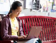 student on a bench with a laptop